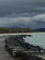 One of jetties and the flag of Saint-Blaise in stormy weather.