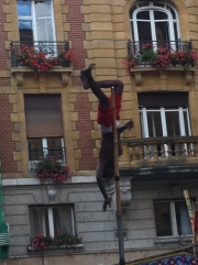 Buskers-8: An Indian up a high pole which was held by a man.