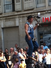 Buskers-2: Knife, umbrella and not sure what, up a pole with a man ...